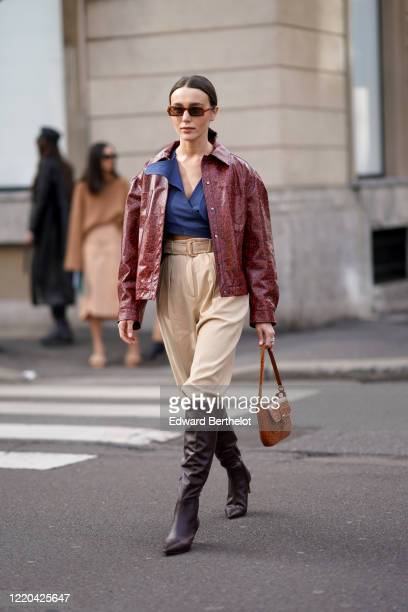 Mary Leest wears sunglasses, a blue shirt, a red/burgundy leather jacket, cream-color beige pants, a brown leather bag, leather high pointy boots,...