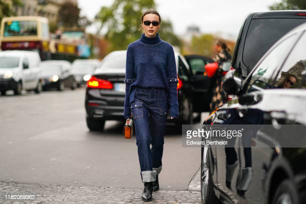 Mary Leest wears sunglasses a blue turtleneck wool pullover with pleated studded sleeves blue denim jeans with large cuffs a brown bag black leather...