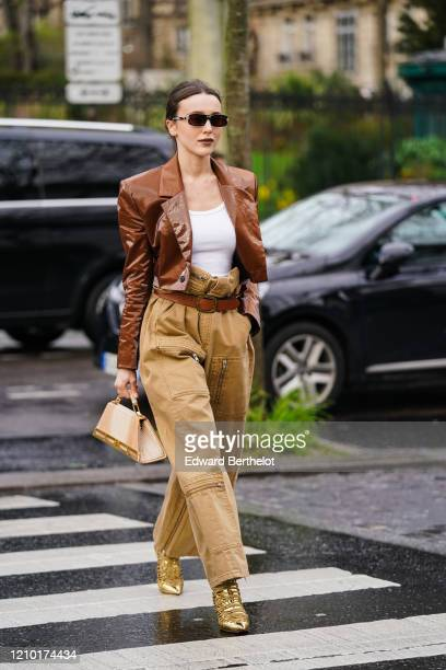 Mary Leest wears sunglasses, a brown shiny jacket, a white t-shirt, a brown leather belt, beige pants with cargo pockets, golden shiny pointy shoes,...
