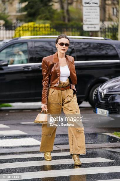 Mary Leest wears sunglasses a brown shiny jacket a white tshirt a brown leather belt beige pants with cargo pockets golden shiny pointy shoes a...