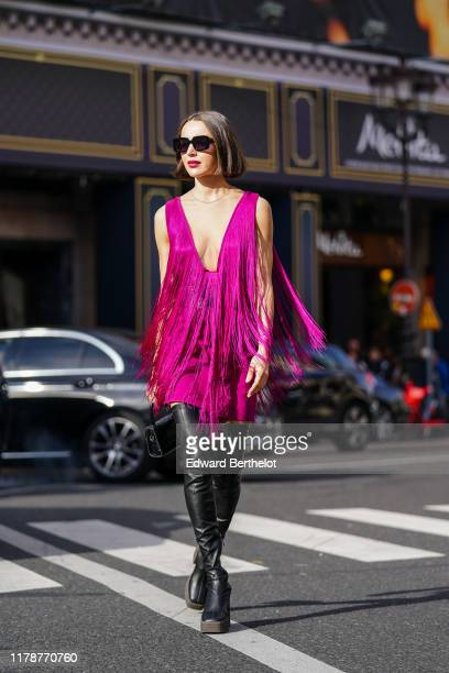 Mary Leest wears sunglasses a fuchsia fringed mini dress with a plunging neckline a large black belt with metallic rings a black crocodile pattern...