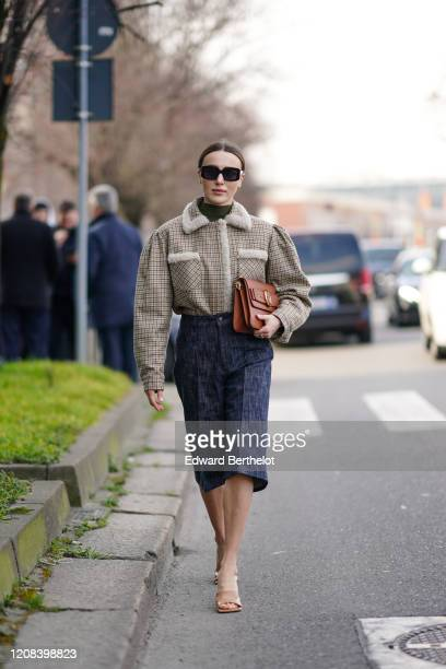 Mary Leest wears sunglasses, a green turtleneck top, an oversized jacket with large sleeves and white wool parts on the collar, a blue denim skirt, a...