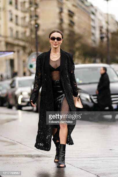 Mary Leest wears sunglasses, earrings, golden necklace, a black mesh lace jacket with floral embroidery, a black fishnet mesh dress, black bras, a...