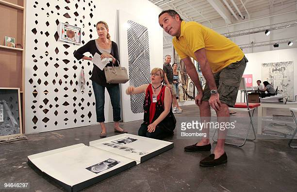 Mary Leigh Cherry center shows the work of artist Amanda RossHo to Renee left and Richard Steinberg of New York at the Cherry and Martin gallery...