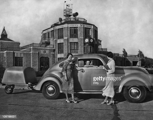 Mary Lou and Jane Houston stand beside a car driven by Betty Ellet which is attached to a single wheel trailer at Akron airport in Ohio in 1934.