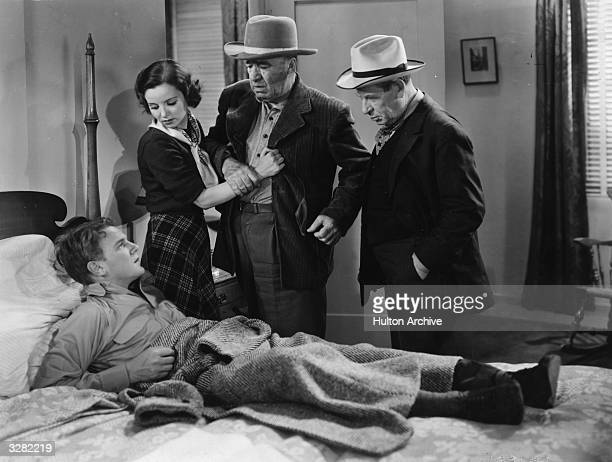 Mary Lou Lender and J Farrell MacDonald visit the bedridden John Arledge in a scene from the sporting drama 'County Fair' directed by Howard...