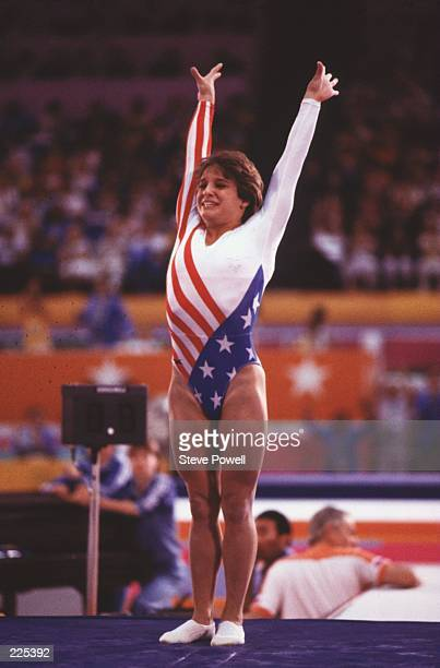 Gymnast Mary Lou Retton of the USA raises her hands in celebration as she salutes the crowd following her performance in the women's floor exercise...