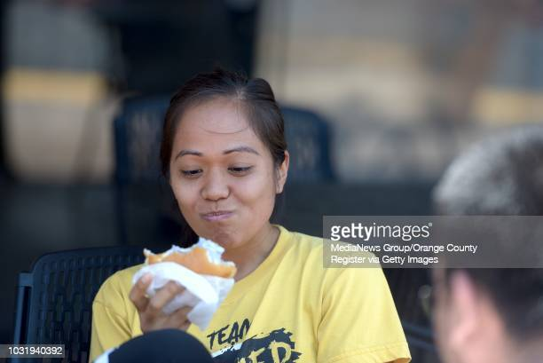 Mary Marasigan takes bites from her ice cream on a milky bun at Afters Handcrafted Ice Cream Fountain Valley on Wednesday The store features ice...