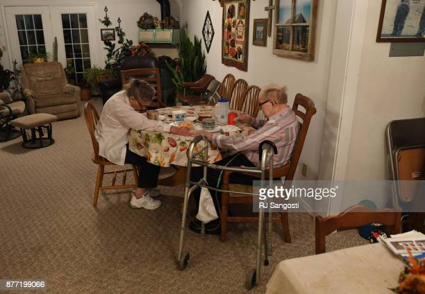Mary May and her husband James Gourley join hands as they pray before a meal on November 13 2017 in Two Buttes Colorado James and Mary May still live...