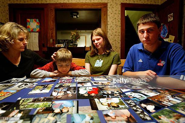 Mary McGurran and her children Noah McGurranHanson Gabrielle McGurranHanson and Isaac McGurranHanson look over family photographs at their...
