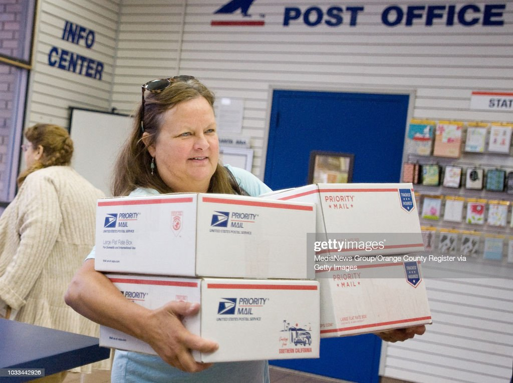 Mary Moss of Santa Ana has her arms full with Christmas gifts to ...