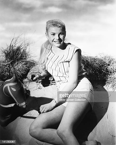 Mary Peach British actress wearing a top with vertical stripes and a pair of white shorts smiling in a studio portrait circa 1955