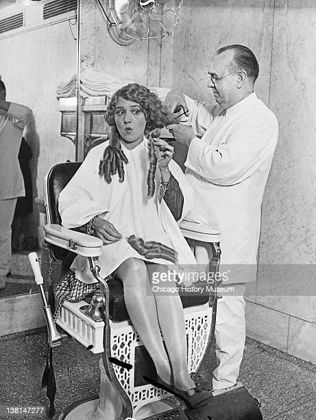 Mary Pickford getting her hair cut sitting in a chair in a barber shop Chicago Illinois 1928