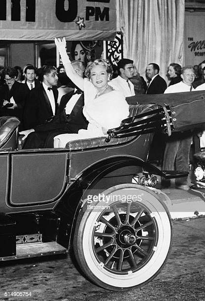Mary Pickford in the back of a vintage 1912 Buick waves to the crowd as she arrives for a benefit premiere in Hollywood
