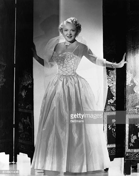 Mary Pickford is shown in an evening gown standing in a doorway This is a publicity photo taken in 1953 when she was 60 years old to promote the sale...