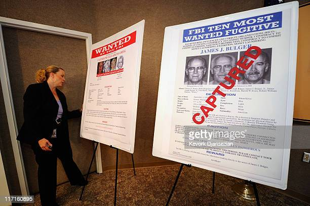 Mary Prang Special Agent wit the FBI adjusts a poster featuring fugitives Boston crime boss James Whitey Bulger along with his companion Catherine...