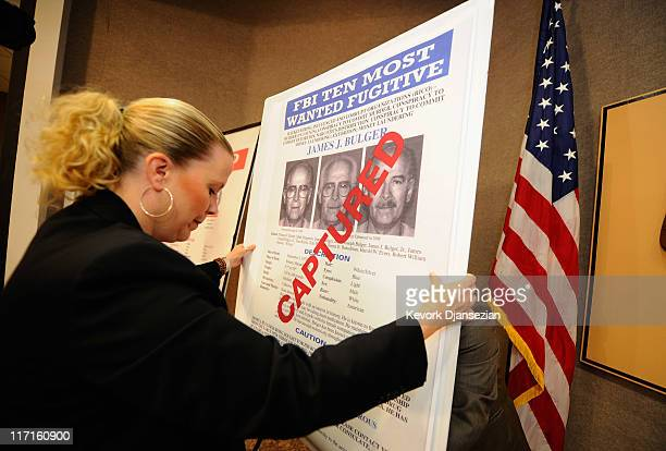 "Mary Prang, Special Agent wit the FBI, adjusts a poster featuring fugitives Boston crime boss James ""Whitey"" Bulger along with his companion..."