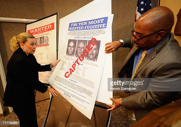 Mary Prang, Special Agent wit the FBI, and Reginald Chapple, FBI Community Outreach Specialist, adjusts a poster featuring fugitives Boston crime...