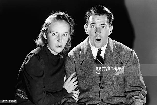 Mary Rumsey and E Cutrer Jr demonstrate startled expressions as they pose in a darkened room Ca 19501960