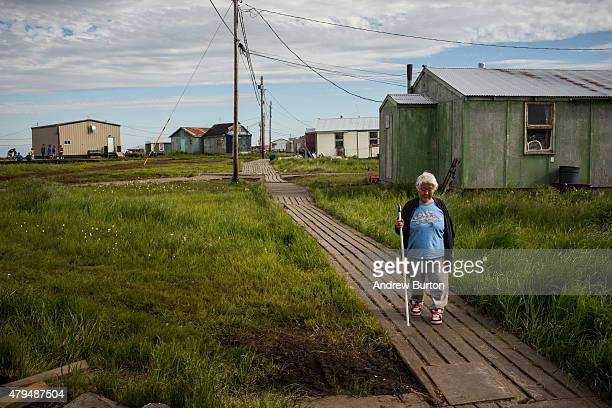 Mary Tom walks down a wooden sidewalk on July 3 2015 in Newtok Alaska Newtok is one of several remote Alaskan villages that is being forced to...