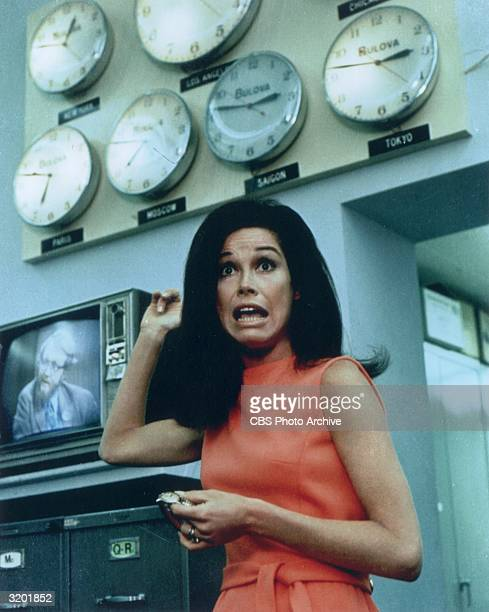 Mary Tyler Moore looks surprised while attempting to set her watch in front of a wall of clocks all of which show different time zones in a...