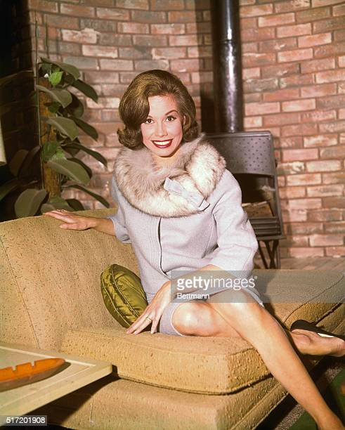 Mary Tyler Moore sitting on a yellow couch wearing a fur collared dress on the set of the Dick Van Dyke Show that ran from 1961-1966.