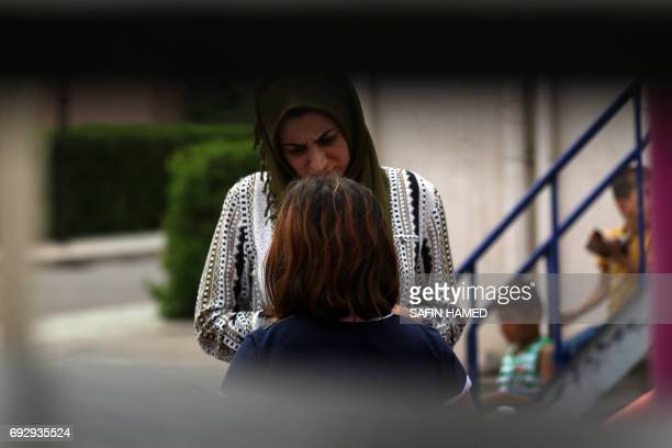 Maryam a 15yearold displaced Iraqi girl from Mosul speaks to an employee of her orphanage in Arbil the capital of the Kurdish autonomous region in...