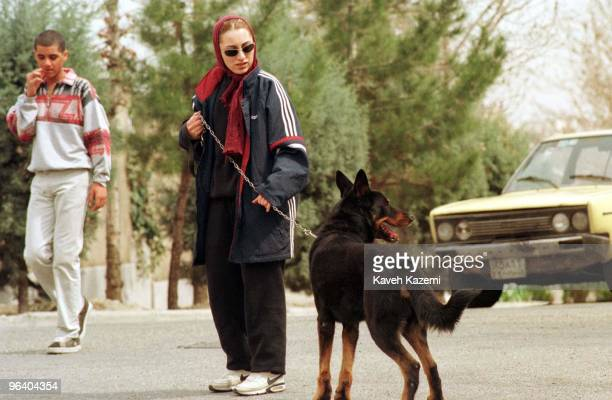 Maryam a 26 year old Iranian architect walks her dog Toby in their neighborhood in Ghods city west Tehran Iran 20th March 1999 Dogs are considered...