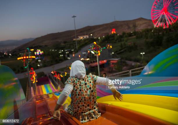 Maryam a young girl who fled with her family from Baquba to the northern city of Zakho goes down the slide at the 'Happy Time' Amusement park as...