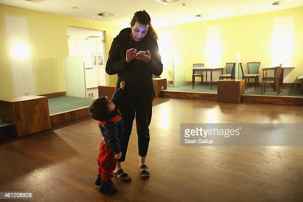 Maryam an Iranian Christian refugee seeking asylum in Germany looks on Facebook on her smartphone as her son Mahan clings to her at the Spreehotel...