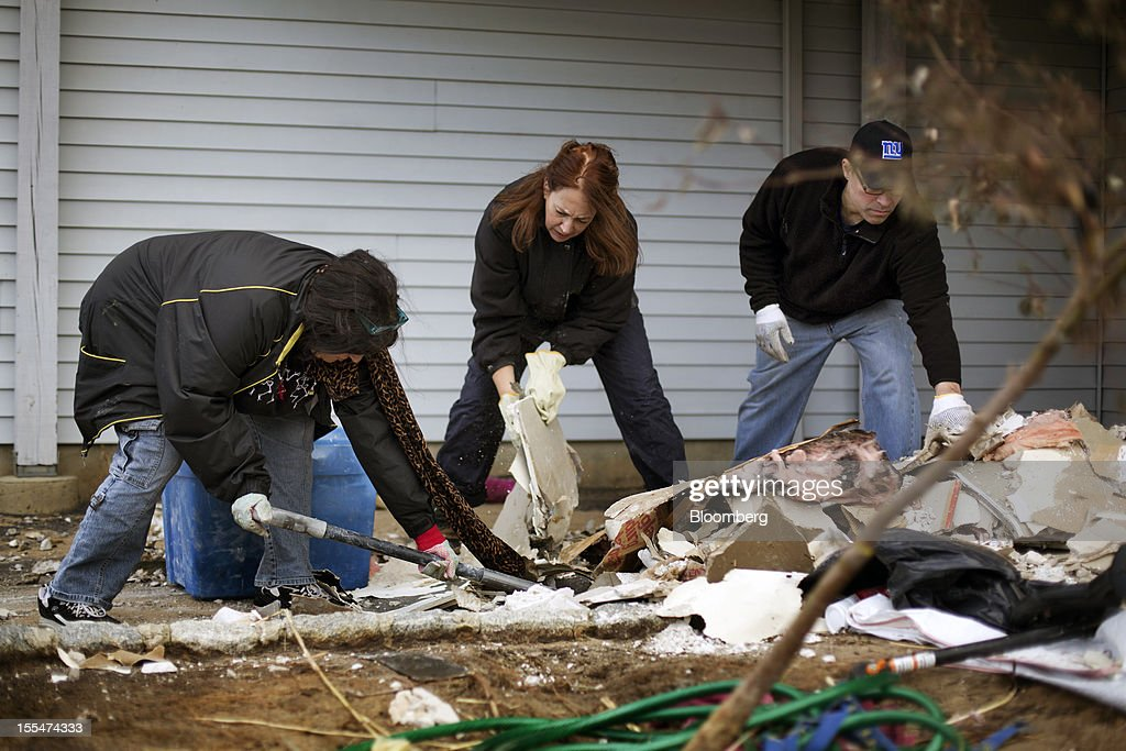 "MaryAnne Hayes, left, shovels debris with her sister Anne Marie Widmer, center, and Tom Musumeci, right, at her daughter Sandy Hayes' home in Union Beach, New Jersey, U.S. on Saturday, Nov. 3, 2012. Recovery progressed slowly in New Jersey, where Hurricane Sandy struck on Oct. 29. New Jersey Governor Chris Christie, a Republican, praised the ""patience and resilience"" of New Jerseyans and released a timeline Saturday of which neighborhoods without electricity should be restored over the next few days. Photograph: Victor J. Blue/Bloomberg via Getty Images"