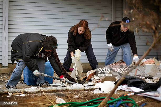 MaryAnne Hayes left shovels debris with her sister Anne Marie Widmer center and Tom Musumeci right at her daughter Sandy Hayes' home in Union Beach...