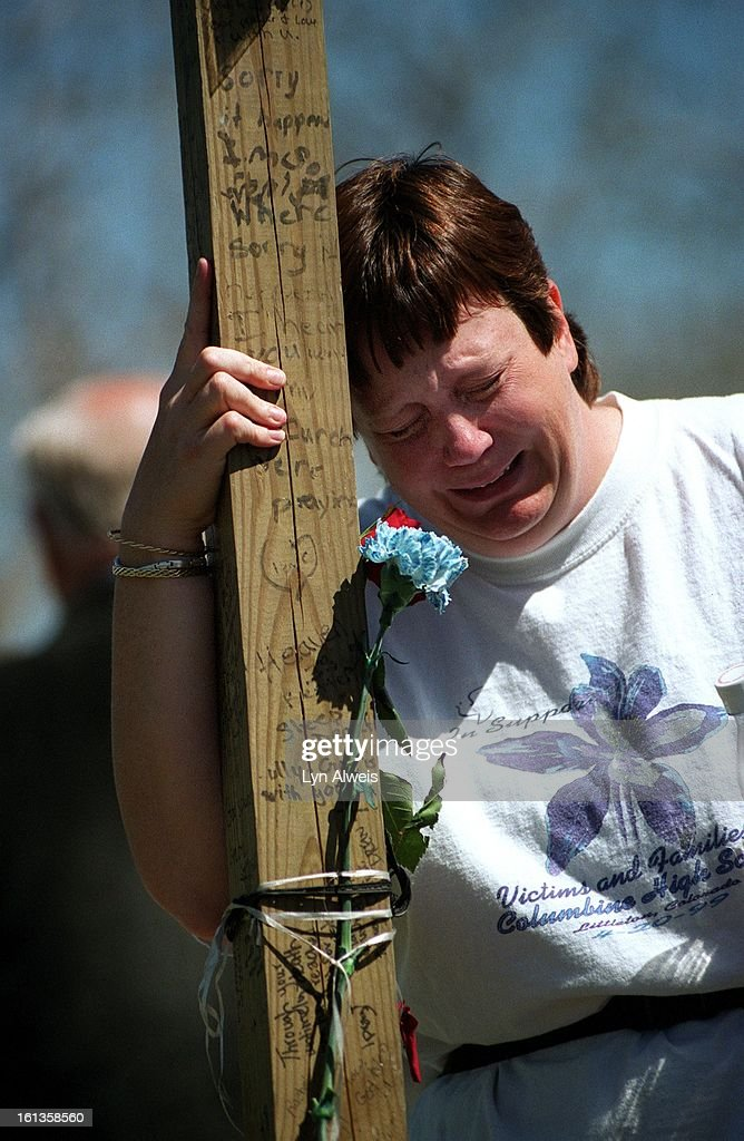MaryAnne Mueller of Littleton breaks down and cries at the cross of Columbine victim Rachel Scott in Clement Park. Greg Zanis, from Aurora, Illonois, brought back the 13 crosses that has been placed in Clement Park one year ago. They were set up on stands : News Photo