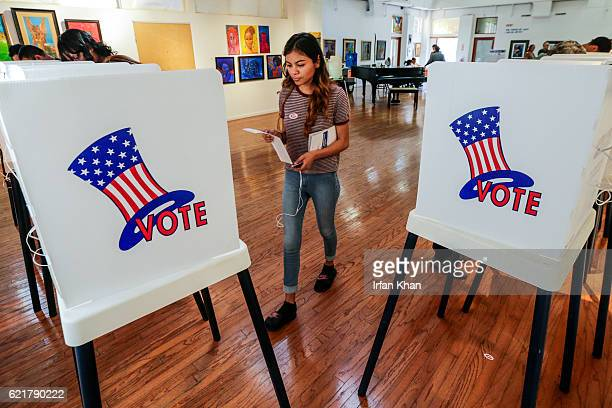 Maryjane Medina a first time voter walks up to polling booth to cast her vote at a polling station setup at Watts Towers Arts Center on November 8...