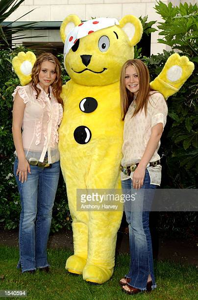 MaryKate and Ashley Olsen pose for a photograph with the Children in Needs Pudsey bear as they present a check to the BBC for Children in Need for...