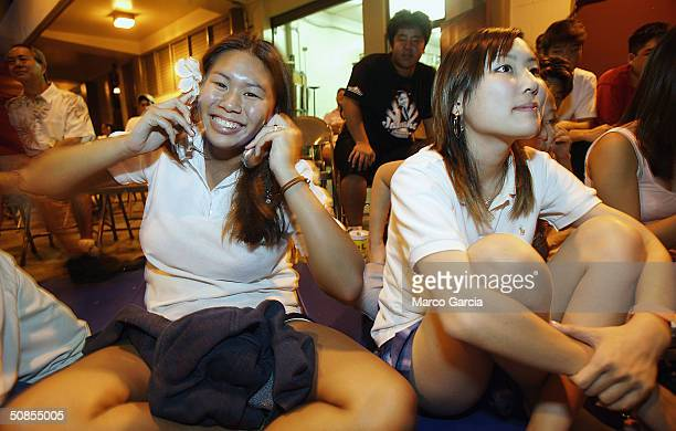 Maryknoll School student Queena Lau uses two cell phones to vote for classmate and American Idol finalist Jasmine Trias May 18 2004 in Honolulu...