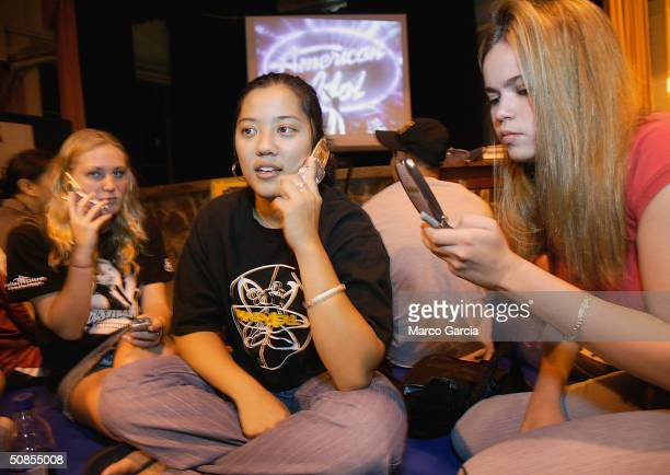 Maryknoll School students Lisa Styring Amanda Ikehara and Catherine Piazza use cell phones to vote for classmate and American Idol finalist Jasmine...