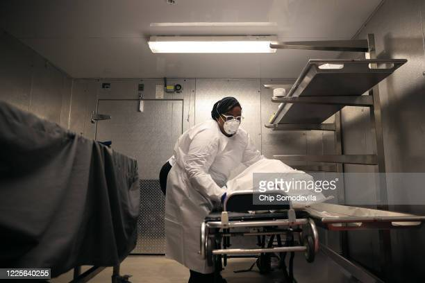 Maryland Cremation Services transporter Morgan DeanMcMillan gently moves the remains of a coronavirus victim onto a stretcher in the morgue at...