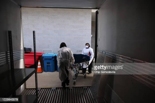 Maryland Cremation Services transporters Emma Tilghman and Morgan Dean-McMillan wheel the remains of a coronavirus victim from inside a refrigerated...