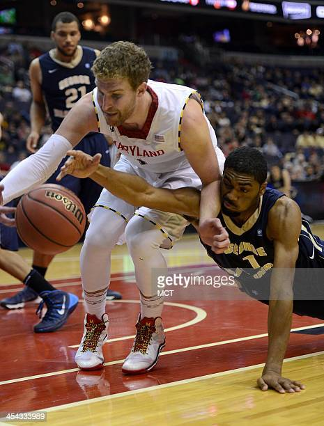 Maryland forward Evan Smotrycz and George Washington guard Maurice Creek go after a ball headed out of bound in the second half of an NCAA basketball...