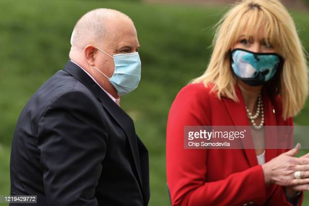 Maryland Governor Larry Hogan and Commerce Secretary Kelly Schulz wear a face masks as they depart a news conference about the ongoing coronavirus...