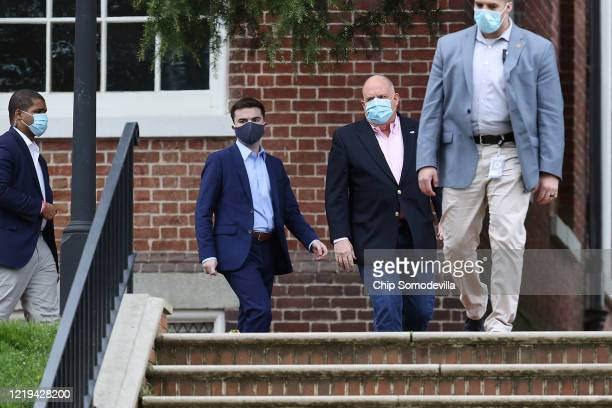 Maryland Governor Larry Hogan is escorted by security as he arrives for a news briefing about the ongoing novel coronavirus pandemic in front of the...