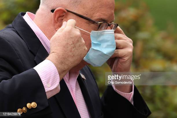 Maryland Governor Larry Hogan replaces his surgical mask after talking to reporters during a news briefing in front of the Maryland State House April...