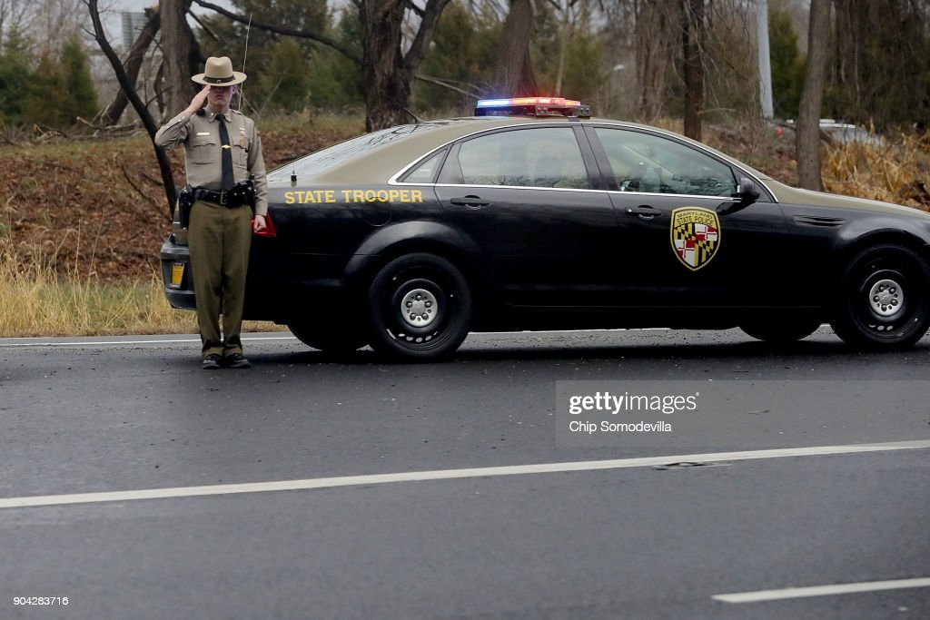 A Maryland State Trooper salutes as U.S. President Donald Trump's motorcade heads to Walter Reed National Military Medical Center for his annual physical examination January 12, 2018 in Bethesda, Maryland. Trump will next travel to Florida to spend the Dr. Martin Luther King Jr. Day holiday weekend at his Mar-a-Lago resort.