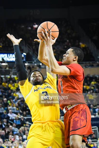 Maryland Terrapins guard Anthony Cowan leans into Michigan Wolverines guard Zavier Simpson trying to draw the foul during the Michigan Wolverines...