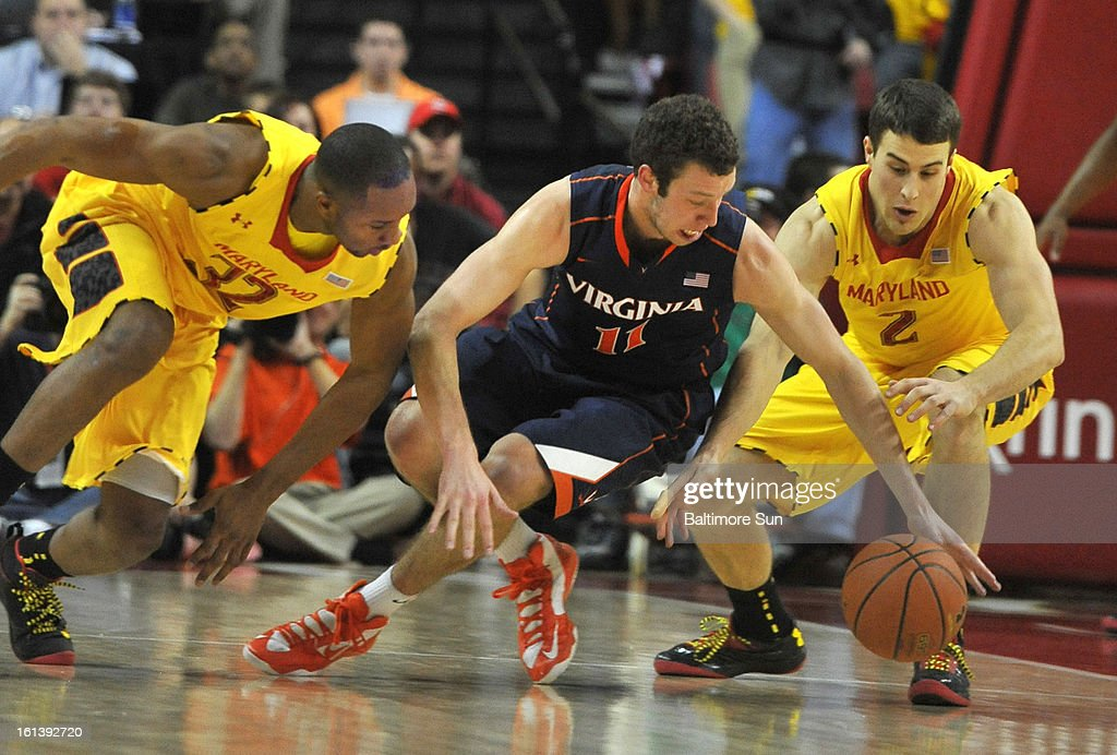 Maryland's Dez Wells, left and Logan Aronhalt, right, and Virginia's Evan Nolte chase a loose ball during a men's college basketball game in College Park, Maryland, Sunday, February 10, 2013. Virginia won, 80-69.