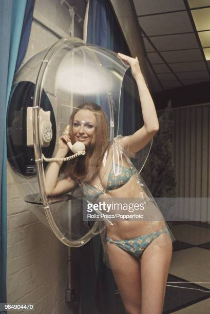 MaryLou Hayden wearing a bikini uses a new seethrough moulded acrylic plastic telephone booth at an exhibition of new telecommunications equipment at...