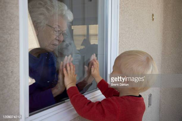 Mary-Lou McCullagh and her husband Bob greet Axel Stirton the little boy who lives across the street April 3, 2020 in Ventura, California. Mary-Lou...