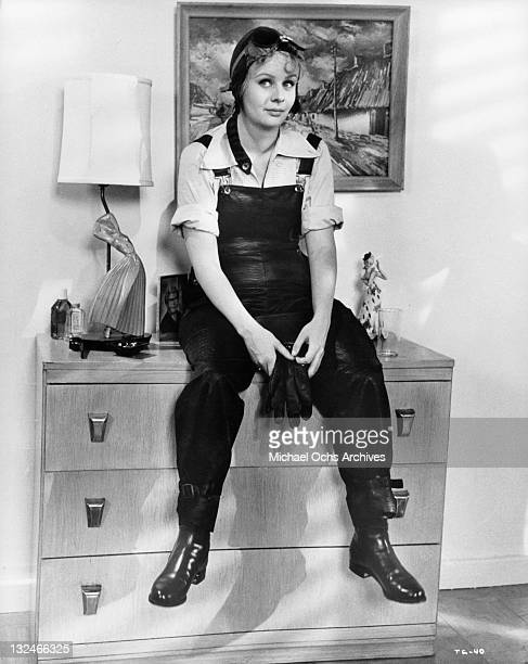 MaryRobin Redd sitting on a chest of drawers in an aviator outfit in a scene from the film 'The Group' 1966