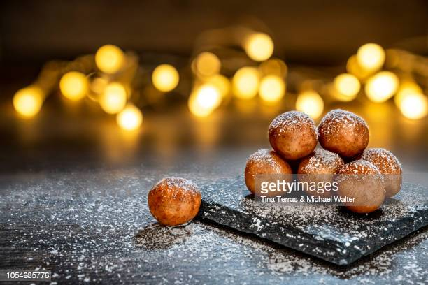 marzipan balls with powdered sugar on wooden board with slate plate and candlelight. - ペストリー生地 ストックフォトと画像